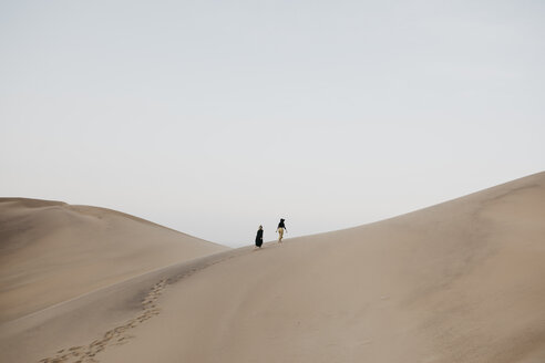 Namibia, Namib, back view of two women walking on desert dune - LHPF00279