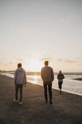 Namibia, Walvis Bay, back view of three friends walking on the beach at sunset - LHPF00285