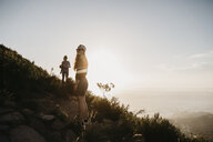 South Africa, Cape Town, Kloof Nek, two women on a trail at sunset - LHPF00288