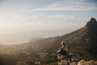 South Africa, Cape Town, Kloof Nek, woman sitting on rock at sunset - LHPF00291