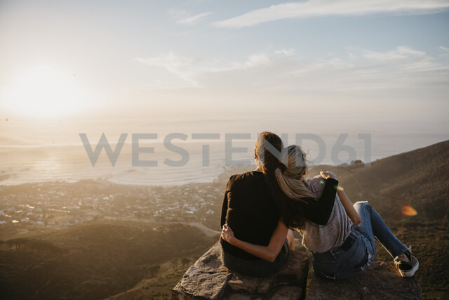 South Africa, Cape Town, Kloof Nek, two women sitting on rock at sunset - LHPF00294 - letizia haessig photography/Westend61