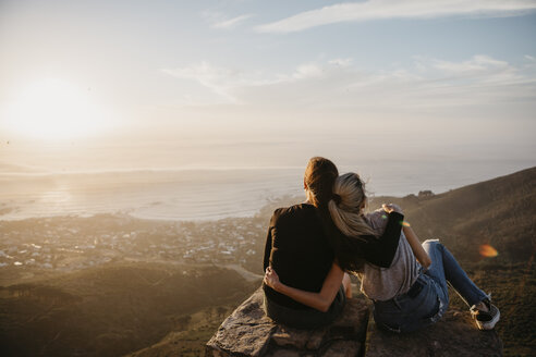 South Africa, Cape Town, Kloof Nek, two women sitting on rock at sunset - LHPF00294
