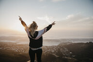 South Africa, Cape Town, Kloof Nek, happy woman enjoying the view at sunset - LHPF00300