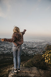 South Africa, Cape Town, Kloof Nek, happy woman enjoying the view at sunset - LHPF00303