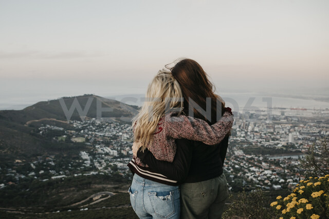 South Africa, Cape Town, Kloof Nek, rear view of two women embracing at sunset - LHPF00306 - letizia haessig photography/Westend61