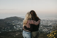 South Africa, Cape Town, Kloof Nek, rear view of two women embracing at sunset - LHPF00306