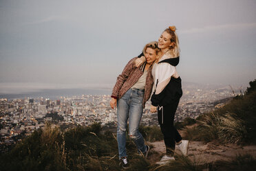 South Africa, Cape Town, Kloof Nek, two happy women embracing at sunset with cityscape in background - LHPF00309