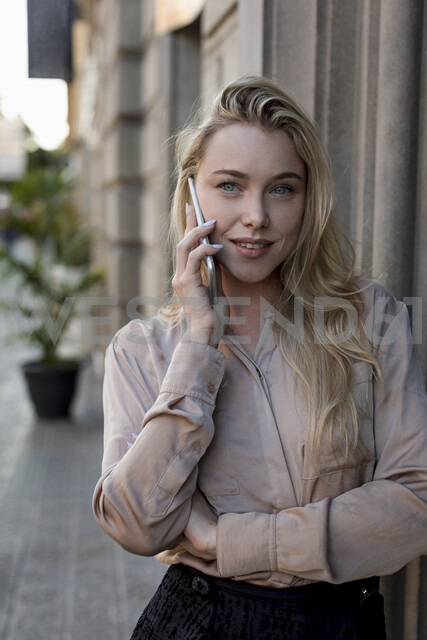 Portrait of beautiful young businesswoman on cell phone in the city - MAUF02107 - Mauro Grigollo/Westend61