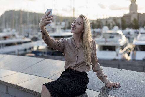 Smiling young woman taking a selfie at the waterfront - MAUF02128