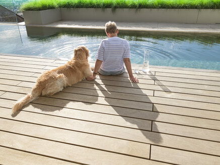 Senior woman sitting with dog at the poolside - LAF02209