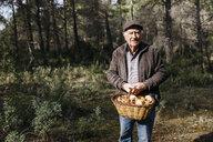 Portrait of smiling senior man holding basket full of mushrooms in the forest - JRFF02248