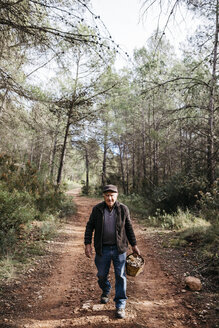 Portrait of smiling senior man walking with basket full of mushrooms in the forest - JRFF02251
