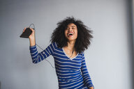 Portrait of happy young woman with smartphone and earphones singing and dancing - KKAF03072