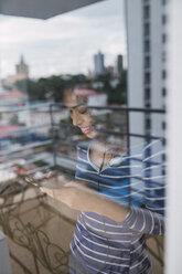 Smiling young woman behind windowpane using smartphone and earphones - KKAF03078