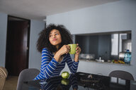 Portrait of young woman drinking coffee and eating an apple at home - KKAF03081