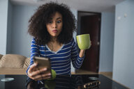 Portrait of young woman with mug starring at cell phone - KKAF03084