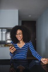 Portrait of happy young woman at home looking at cell phone - KKAF03093