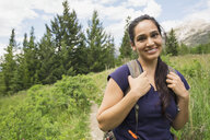 Portrait of smiling woman on hiking trail - HEROF02296