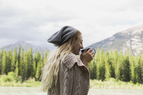 Woman drinking coffee near mountains - HEROF02365