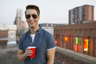 Portrait of smiling man drinking on urban rooftop - HEROF02383