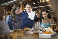 Waiter serving food to friends in pub - HEROF02443