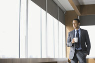 Businessman drinking coffee in conference room - HEROF02485