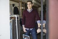 Business owner with Open sign in shop doorway - HEROF02560