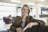 Portrait of smiling woman waiting in airport - HEROF02626