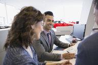 Salesman and couple finalizing paperwork in car dealership - HEROF02665