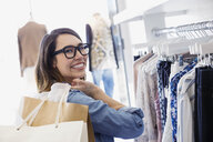 Portrait of smiling woman shopping in clothing store - HEROF02698