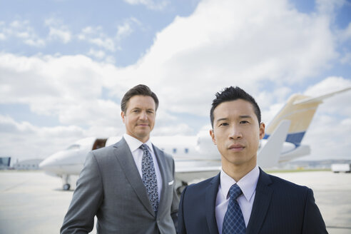 Portrait of businessmen on tarmac with corporate jet - HEROF02701