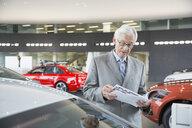 Man with brochure in car dealership showroom - HEROF02731