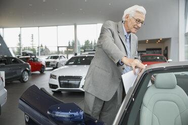 Man looking inside convertible in car dealership showroom - HEROF02749