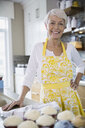 Portrait of smiling woman baking cupcakes in kitchen - HEROF02761