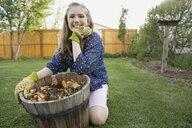Portrait of smiling girl with flowerpot in garden - HEROF02767