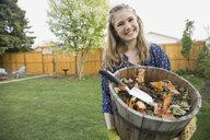 Portrait of smiling girl with flowerpot in garden - HEROF02770