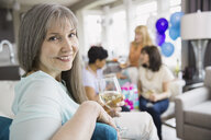 Portrait of smiling woman at party in living room - HEROF02773