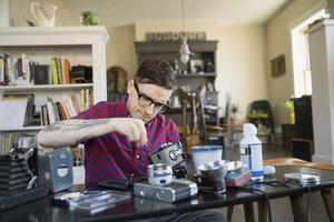 Man repairing antique camera in living room - HEROF02791