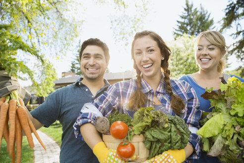 Portrait of friends holding freshly harvested vegetables - HEROF02821