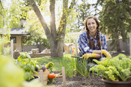 Portrait of smiling woman in vegetable garden - HEROF02824