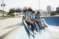 Teenage boys sitting at edge of skateboard ramp - HEROF02950