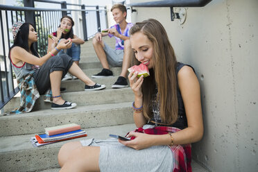Teenager with cell phone eating watermelon on stairs - HEROF02968