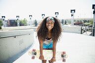 Portrait of teenage girl holding skateboard - HEROF03001