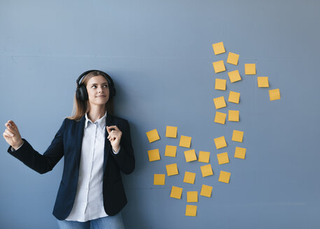 Young businesswoman wearing headphones, listeining music - GUSF01672