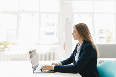 Young businesswoman sitting in office, using laptop - GUSF01675