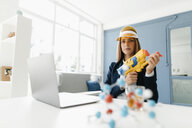 Female scientist holding water gun, studying molecules - GUSF01684