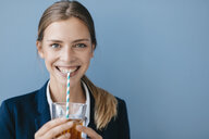 Portrait of a young businesswoman against blue background, drinking iced tea with a straw - GUSF01693