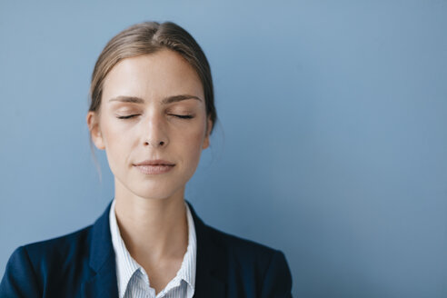 Portrait of a young businesswoman against blue background, relaxing with eyes closed - GUSF01696
