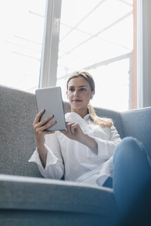 Young woman sitting on couch, using digital tablet - GUSF01702