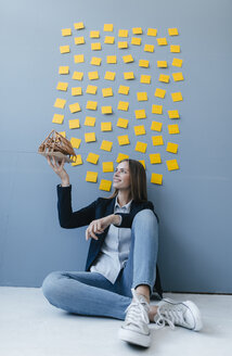 Young businesswoman holding architectural model with yellow sticky notes on the wall behind ger - GUSF01714